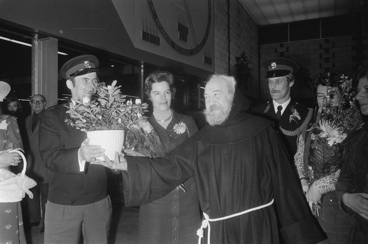 Vereniging Bloemenveilingen Aalsmeer huldigt korps Rijkspolitie. Acteur Lex Goudsmit (als Broeder Valentijn) deelt bloemen uit. Foto Hans Peters / Anefo (CC BY-SA 3.0 NL).